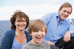 Parents with son in front of photo-voltaic panel