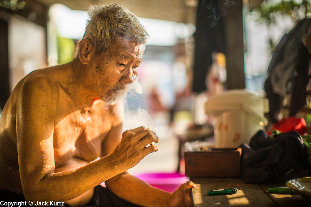 17 JANUARY 2013 - DAMNOEN SADUAK, RATCHABURI, THAILAND: A resident of Damnoen Saduak (also spelled Damnoensaduak) smokes his cigarette of the day in front of his on the Damneon Saduak canal. The floating market in Damnoen Saduak is one of the best known tourist attractions in Thailand. The canal was dug in the 1860's to connect to provincial towns south of Bangkok. At the time it was the straightest, longest canal in Thailand. Thousands of tourists, both foreign and Thai, visit Damnoen Saduak to see the floating market and experience canal life.     PHOTO BY JACK KURTZ