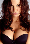 Wavy hair covering part of a woman's pouting face. Woman with generous cleavage wearing a black push up top.