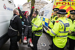 © Licensed to London News Pictures . 01/10/2017. Manchester, UK. Police arrest wheelchair users amongst anti Tory protesters blocking tramtracks at St Peter's Square opposite the Midland Hotel . People take part in a demonstration against the Conservative Party in Manchester during the Conservative Party Conference , which is taking place at the Manchester Central Convention Centre . Photo credit: Joel Goodman/LNP