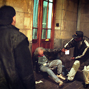 Evangelists help a drunk to his feet at Amsterdam's central station. ..Victory Outreach, a controversial church started in Los Angeles in 1967, is spreading to Europe via the Netherlands. It builds its membership among junkies, prostitutes and criminals. ..Photo taken in the Netherlands in 2002. The picture is part of a photo and text documentary by Justin Jin. For more information, email justin@justinjin.com