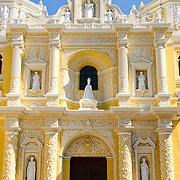Main entrance of the distinctive  and ornate yellow and white exterior of the Iglesia y Convento de Nuestra Senora de la Merced in downtown Antigua, Guatemala.