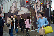 People walk past a giant models on a hoarding for a fashion outlet on Oxford Street, London, UK. Little people against the large scale wall.
