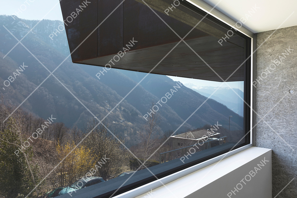 Very large window detail with a view of the panorama of the Swiss mountains in Ticino. Nobody inside