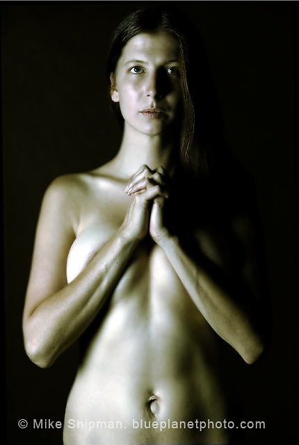 nude woman standing with arms and hands clasped in front of her breasts. Toned image.