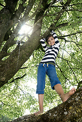Girl climbing on tree and smiling, Munich, Bavaria, Germany