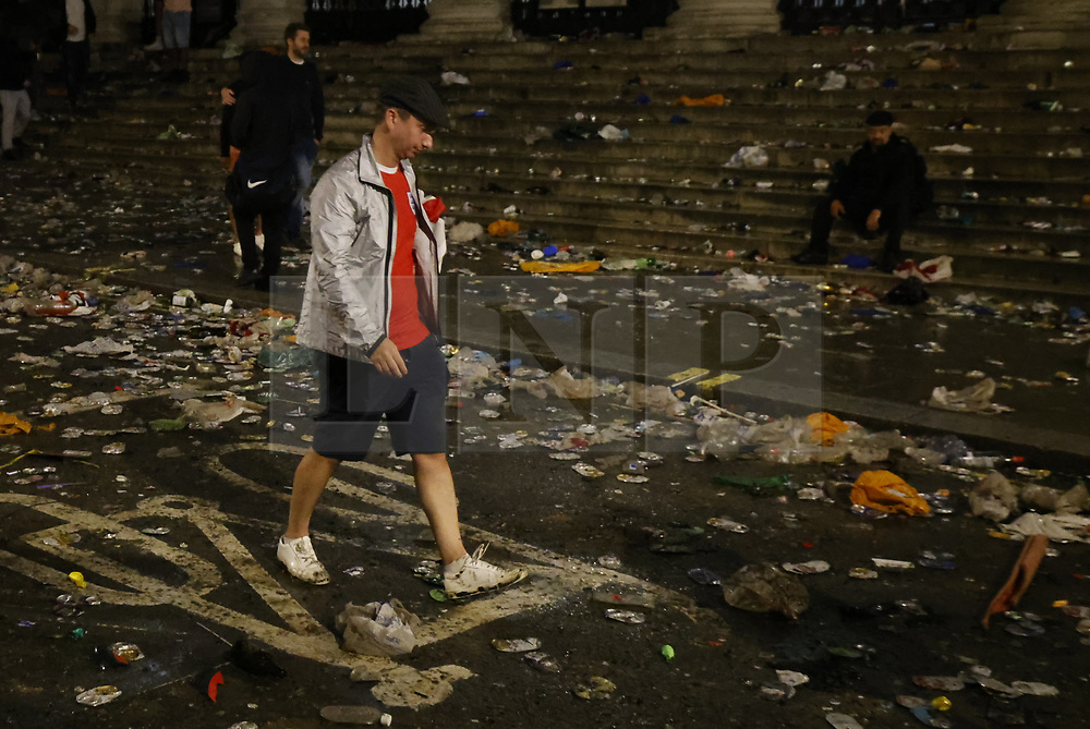 © Licensed to London News Pictures. 11/07/2021. London, UK. England supporters head home through litter strewn streets after losing at the EURO 2020 final to Italy on penalties as they watch the giant screens in Tragalgar Square, central London. Photo credit: Peter Macdiarmid/LNP