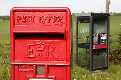 Postbox and telephone box in rural setting,