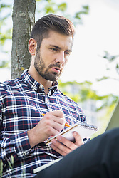 Young man sitting in a park and writing in notepad, Munich, Bavaria, Germany