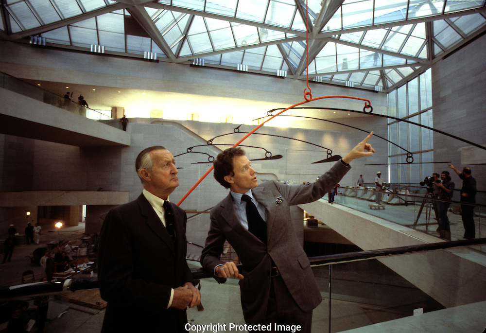 Paul Mellow and J. Carter Brown talk in  the East Building of the National Gallery of Art during the installation of the Calder mobile in  May 1978...Photograph by Dennis Brack BB23