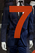 Trendy blue suits with red prices and lettering on display in a central London menswear shop. The number Seven is positioned across the chest of one of three mannequins in the window of the store - the 7 denoting part of the price of these items of clothing. The shop is on London's Oxford Street, an east to west road long known for clothing and low-cost fashion - and before that, for the route that condemned criminals would take towards the gallows at nearby Tyburn.