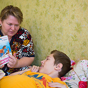 CAPTION: Lybov's son Erik was born with multiple severe disabilities. He has been bed-bound for the past two months, following surgery on his leg. During this time, he has stayed entertained by listening to fairy tales on the Internet. LOCATION: St Petersburg, Russia. INDIVIDUAL(S) PHOTOGRAPHED: Lybov Chusheva (mother) and Erik Chushev (son).