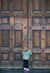 © Licensed to London News Pictures. 22/10/2011. London, UK. 2-year-old Holly (permission given by parents to use picture) tries to push open the doors of St Paul's cathedral which is closed due to the ongoing Occupy London demo. Protestors from 'Occupy London', who are targeting the global financial system as part of a worldwide campaign against corporate greed, have spent their seventh night camped outside St Paul's Cathedral which is adjacent to The London Stock Exchange. Photo credit: Ben Cawthra/LNP