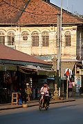 A man drives by old colonial architecture in Siem Reap, Cambodia