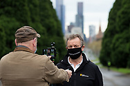 MELBOURNE, VIC - SEPTEMBER 12: A man who claims to be a local, wearing an anti Daniel Andrews facemask stops to speak to the media before being arrested during the Melbourne Freedom Walk Rally on September 12, 2020 in Melbourne, Australia. Stage 4 restrictions are in place from 6pm on Sunday 2 August for metropolitan Melbourne. This includes a curfew from 8pm to 5am every evening. During this time people are only allowed to leave their house for work, and essential health, care or safety reasons. Despite this, multiple protests are being arranged to push back against the draconian restrictions in place within metropolitan Melbourne. A Freedom Walk was arranged to take place in the Tan but with hundreds of police and wet weather forecast, only a small number of protesters tried to attend before being ordered to move on. (Photo by Dave Hewison/Speed Media)
