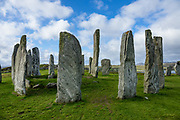 "Erected 4600 years ago, the Callanish Standing Stones are one of the most spectacular megalithic monuments in Scotland. The main site known as ""Callanish I"" forms a cross with a central stone circle erected circa 2900-2600 BC. More lines of stones were added by 2000 BC (the close of the Neolithic era), and it become a focus for rituals during the Bronze Age. From 1500-1000 BC, farmers emptied the burials and ploughed the area. After from 800 BC, peat accumulated 1.5 meters deep and buried the stones until removed in 1857. Visit this spectacular ancient site near the village of Callanish (Gaelic: Calanais), on the Isle of Lewis, Outer Hebrides (Western Isles), Scotland, United Kingdom, Europe."