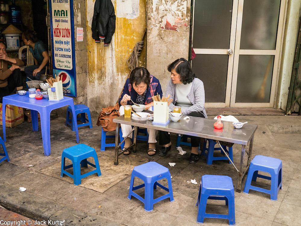 02 APRIL 2012 - HANOI, VIETNAM: Women eat lunch at a street stall in Hanoi, the capital of Vietnam.    PHOTO BY JACK KURTZ