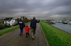 Walking along the top of a small dike in Burghsluis, the Netherlands, that protects the village on the left from the sea on the right. Most of the Netherlands is at or below sea-level, and would be flooded if not for the intricate system of dikes, dams and storm surge barriers. Burghsluis is a small village located next to the Eastern Scheldt Storm Surge Barrier, which is the Netherlands main defense against flood waters from the North Sea. The Netherlands, situated on the North Sea at the delta of three major rivers, the Rhine, the Mass and the Scheldt, is a country wrested from the sea. After a series of major floods, the last occurring in 1953, the Dutch government implemented the Delta Project. This ambitious hydraulic engineering project which spanned 15 years, closed off the the main tidal estuaries and inlets in the southwestern part of the Netherlands, with the exception of those giving access to the Ports of Rotterdam and Antwerp. To add some perspective, the storm surge that caused the 1953 flood, would not even reach the caution level on the current storm surge barrier. (Photo © Jock Fistick)