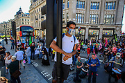 An XR activist observes the protests from a traffic light at Oxford Circus junction during a two-week protest campaign in central London on Wednesday, Aug 25, 2021.  XR's protest campaign enters its 3rd day of activities putting at a halt the parts of important junctions in Britain's capital. XR launched a two-week protest campaign in London on Monday to demand that the government take greater action to address climate change. (VX Photo/ Vudi Xhymshiti)
