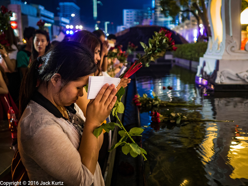 18 FEBRUARY 2016 - BANGKOK, THAILAND: A woman prays for love after presenting nine red roses at the Trimurti Shrine in Bangkok. Every Thursday night, starting just after sunset and peaking at 21.30, hundreds of Bangkok single people, or couples seeking guidance and validation, come to the Trimurti Shrine at the northeast corner of Central World, a large Bangkok shopping mall, to pray to Lord Trimurti, who represents the trinity of Hindu gods - Brahma, Vishnu and Shiva. Worshippers normally bring an offering of red flowers, fruits, one red candle and nine incense sticks. It's believed that Lord Trimurti descends from the heavens at 21.30 on Thursday to listen to people's prayers. Although most Thais are Buddhists, several Hindu traditions have been incorporated into modern Thai Buddhism, including reverance for Trimurti.       PHOTO BY JACK KURTZ