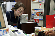 senior woman working behind the counter at a convenient store Japan