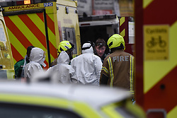 © Licensed to London News Pictures. 01/04/2020. London, UK. Ambulance workers and the fire brigade at an incident involving all emergency services where a suspected COVID-19 case was isolated and removed from their home. Uxbridge Road in Shepherd's Bush was closed for an hour as ambulance, fire brigade and police attended, extracting the patient by crane from a three story apartment building in West London. PPE (personal protective equipment) was in evidence, with the fire brigade using full face respirators normally reserved for firefighting. A police officer commented the Metropolitan police force are issued only with rubber gloves. Ambulance workers decontaminated the scene and reusable equipment before moving on.  Photo credit: Guilhem Baker/LNP