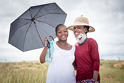 3 March 2017, Thaba Bosiu, Lesotho: Friends Ntaoleng Tlali (right) and Mapontsi Ntjelo (left) from the village of Thaba Bosiu visits the mountain of Thaba Bosiu ('Night Mountain'). Tlali has recently been in a car accident, after which she is wearing neck support as a precaution against further complications. Thaba Bosiu is a sandstone plateau some 24 kilometers east of Lesotho's capital, Maseru. The name means Night Mountain, and surrounding the plateau is a small village and open plains. Thaba Bosiu was once the capital of Lesotho, and the mountain was the stronghold of the Basotho king when the kingdom of Lesotho was formed.