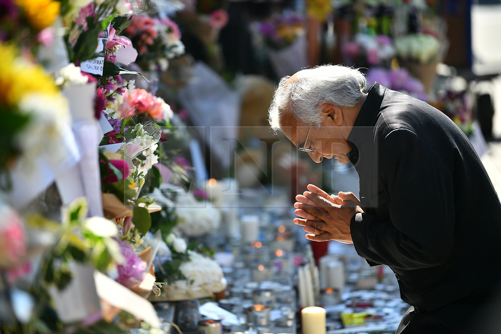 © Licensed to London News Pictures. 17/06/2017. London, UK. A man prays at flowers left at the scene of a fire at the Grenfell tower block in west London earlier this week. The blaze engulfed the 27-storey building killing 12 - with 34 people still in hospital, 18 of whom are in critical condition. The fire brigade say that they don't expect to find anyone else alive. Photo credit: Ben Cawthra/LNP