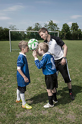 Soccer coach helping young football players