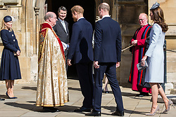 Windsor, UK. 21st April 2019. The Duke of Sussex, followed by the Duke and Duchess of Cambridge, shakes the hand of the Dean of Windsor, the Rt Revd David Conner KCVO, as he arrives to attend the Easter Sunday service at St George's Chapel in Windsor Castle.