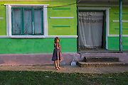 A roma girl in Valea Seaca Village in Bacau County, Romania, stands in front of a house where the wake for a deceased male relative is going on. The girl is eating grapes.