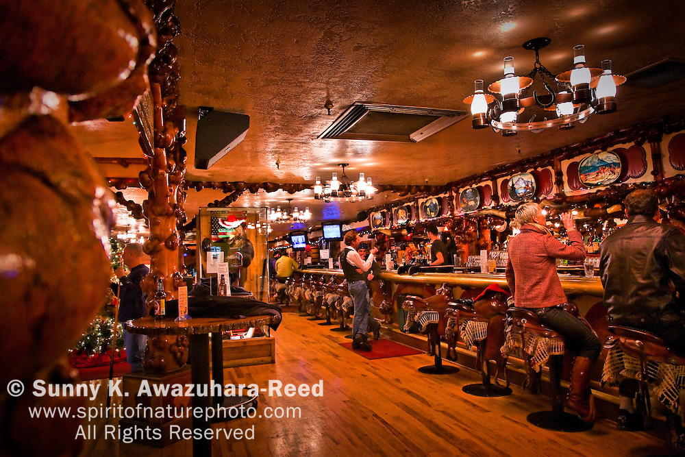 People drinking on horse saddle chair.  The interior of The Million Dollar Cowboy Bar in Jackson Hole, WY.  Christmas Decoration.