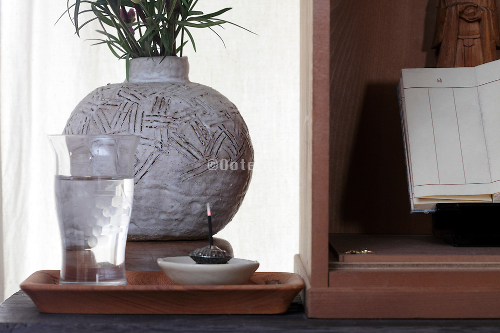 flower water  incense and a little book at home family shrine Japan