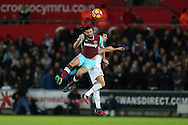 Andy Carroll of West Ham United jumps for a header with Jack Cork of Swansea city. Premier league match, Swansea city v West Ham United at the Liberty Stadium in Swansea, South Wales on Boxing Day, Monday 26th December 2016.<br /> pic by  Andrew Orchard, Andrew Orchard sports photography.