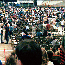 Detail of crowd right of center. A slice of the full Interior of the Venue before the start of the Grateful Dead in Concert at the Carrier Dome, Syracuse University, New York on the 20th of October 1984. Photographed Dead Center Rear view Forward.
