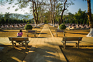 Young woman sits on a bench beside the military cemetary of Doc Lap Hill 'Gabrielle,' the resting place of an estimated 2432 Vietnamese soldiers, Muong Thanh Valley, Dien Bien Province, Vietnam, Southeast Asia