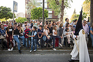 People of all ages line up in a main street of Cordoba to watch the passing of the processions during the Holy Week. Andalusia, Spain,