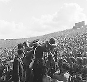 Women being helped over the railing by spectators and guards at the All Ireland Senior Gaelic Football Final Down v. Offaly in Croke Park on the 24th September 1961. Down 3-6 Offaly 2-8.