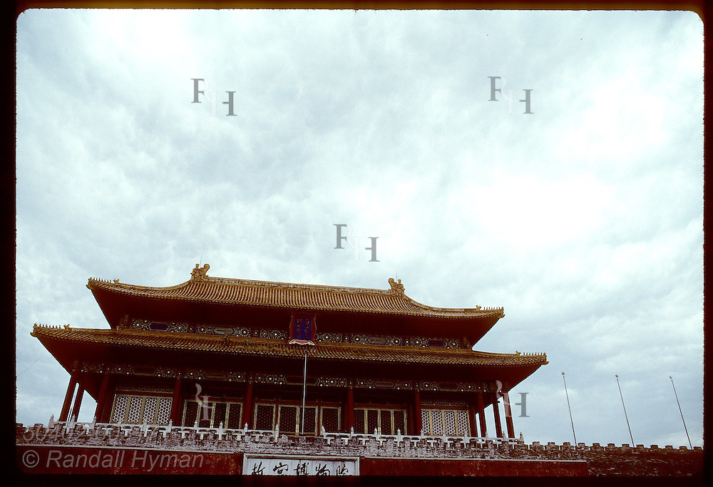 Stormy sky outlines tiered roof of building that is part of outer wall of Forbidden City; Beijing. China