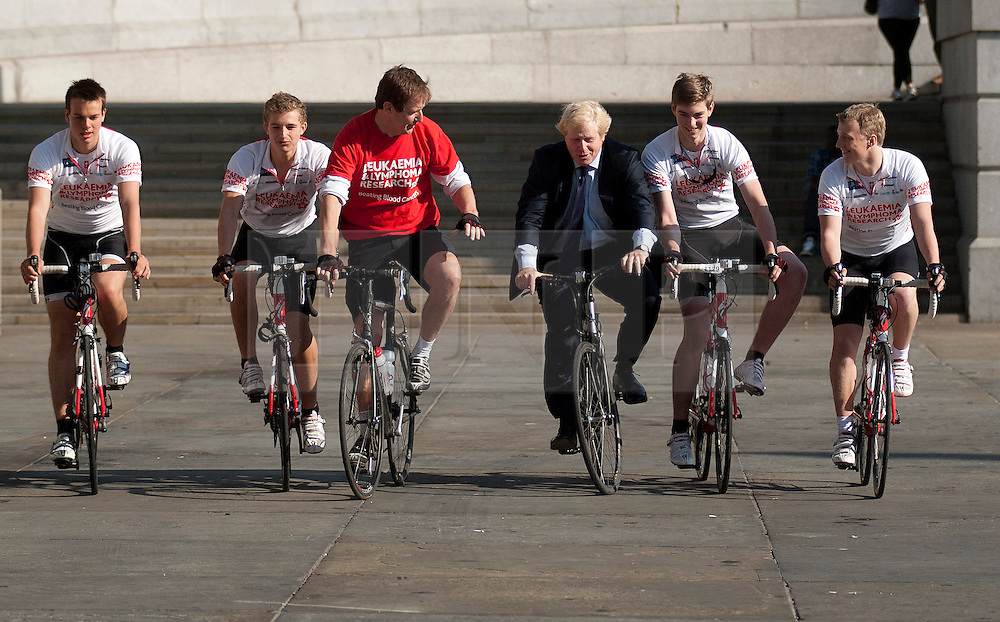 © Licensed to London News Pictures. LONDON, UK  05/07/11. As Alastair Campbell, Chairman of Fundraising at Leukaemia and Lymphoma Research, watches on the Mayor of London, Boris Johnson, wobbles unsteadily on his bike. The pair were riding in Trafalgar Square alongside four school boys who are set to cycle from London to Lisbon in aid of the blood cancer charity. Alastair Campbell, L-R Harry Pearson-Gregory (16), Louise Metcalfe (17), Alastair Campbell, Boris Johnson, Archie Gilmour (17, Boris Johnson's godson) and Tom Prebenson (16), for more information see www.beatbloodcancers.org. Please see special instructions for usage rates. Photo credit should read Matt Cetti-Roberts/LNP