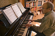 Bjorn Thoroddson of the Thoroddson family, playing piano in his home in Hafnarfjordur, near Reykjavik, Iceland. The Thoroddsons were originally photographed in 1993 for the book Material World, but are seen here in 2004 on a revisit. MODEL RELEASED.