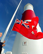 A lighthouse keeper raises the Trinity House flag at Portland Bill lighthouse; Dorset, UK. Portland Bill Lighthouse was demanned on 18th March 1996 when monitoring and control of the station was transferred to the Trinity House Operations & Planning Centre at Harwich.
