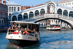 Waterbuses or Vaporetti travelling on the Grand Canal beneath the famous Rialto Bridge in Venice Italy