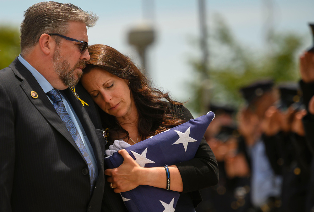 Kelley O'Sullivan leans into her husband Denis O'Sullivan while their daughter's casket is loaded into the hearse following the memorial service for fallen officer Tara O'Sullivan at Bayside Church Adventure Campus, Thursday, June 27, 2019.