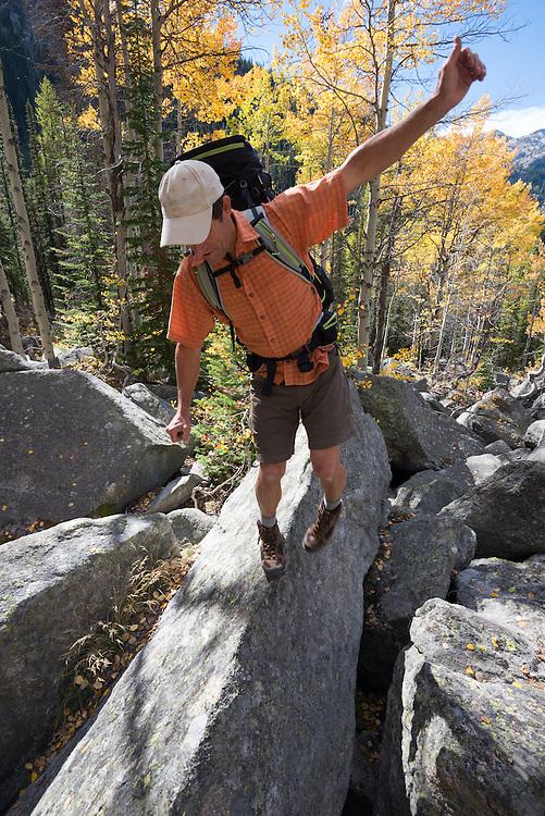 Backpacker balancing as he walks along the narrow top edge of a boulder in Oregon's Wallowa Mountians.