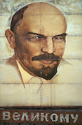 """Ulyanovsk, Urals Region, central  Russia, 1994..A rusting poster of Lenin on a factory wall with the word """"great"""" hanging from it. The birthplace of Vladiimr Lenin, founder of the Soviet Union, remains true to his Communist ideals. There is little private ownership, and all city industry and local agriculture is controlled by the state.."""
