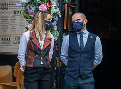 © Licensed to London News Pictures. 22/09/2020. London, UK. Pub workers wear a face masks while serving customers in Covent Garden as the Government announce that all shop staff will have to wear a face masks. Prime Minister Boris Johnson revealed today further tougher Covid restrictions with a 10pm curfew on pubs and restaurants, all shop staff to wear face masks and a £200 fine for not wearing a mask as a spike in coronavirus rates continues across the country. Photo credit: Alex Lentati/LNP