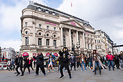 Passers by join in together with some group formation dancing at Piccadilly Circus on 11th April 2021 in London, United Kingdom. After months of lockdown the participants were full of joy and togetherness to be out and about in town and having fun with so many other people.