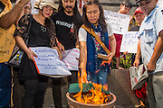 25 JANUARY 2013 - BANGKOK, THAILAND:  Free speech activists in Bangkok burn legal documents related to the Lese Majeste trial of magazine editor Somyot Prueksakasemsuk and freedom of speech in Thailand. About 70 people protested on behalf of freedom of speech and expression at the Criminal Court building in Bangkok Friday. The protest was called as a result of the 10 year sentence handed down against Somyot on Lese Majeste charges earlier in the week. The protesters burned several legal documents to demonstrate they said was their loss of free speech during the protest.    PHOTO BY JACK KURTZ