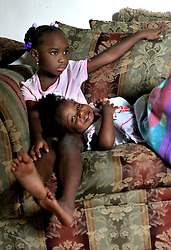 09 July 2006. New Orleans. Louisiana. <br /> Finding Faith. <br /> Faith Figueroa. A day in the life of. Faith (lying down) and her sister Anfernya sit watching cartoons on TV on a rainy Sunday afternoon.<br /> Following a ten month search for the little girl whose face appeared on the Sept 19th, 2005 cover of Newsweek magazine, Faith's mother, Miriam Figueroa has returned to town with her three children. Faith, (1 yrs), Anfernya (5yrs) and Jacquelyn (13 yrs). <br /> Credit; Charlie Varley/varleypix.com